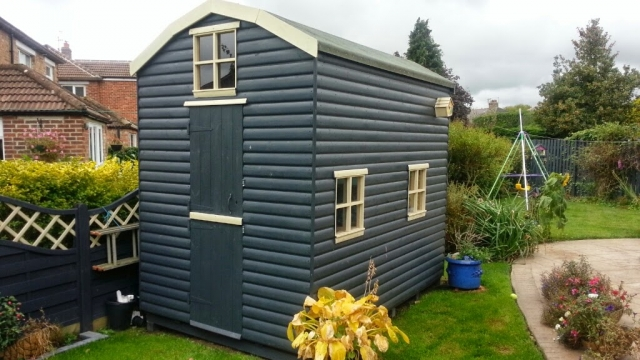 Shiplap cladding painted in grey with cream windows and detailing.