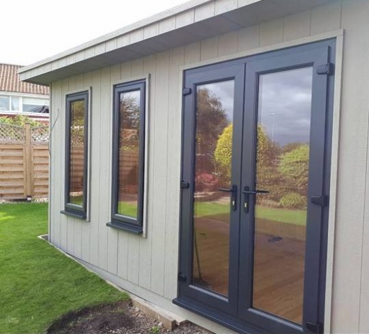 Garden room with LP Strongcore Cladding finished in mist grey with UPVC doors and windows.