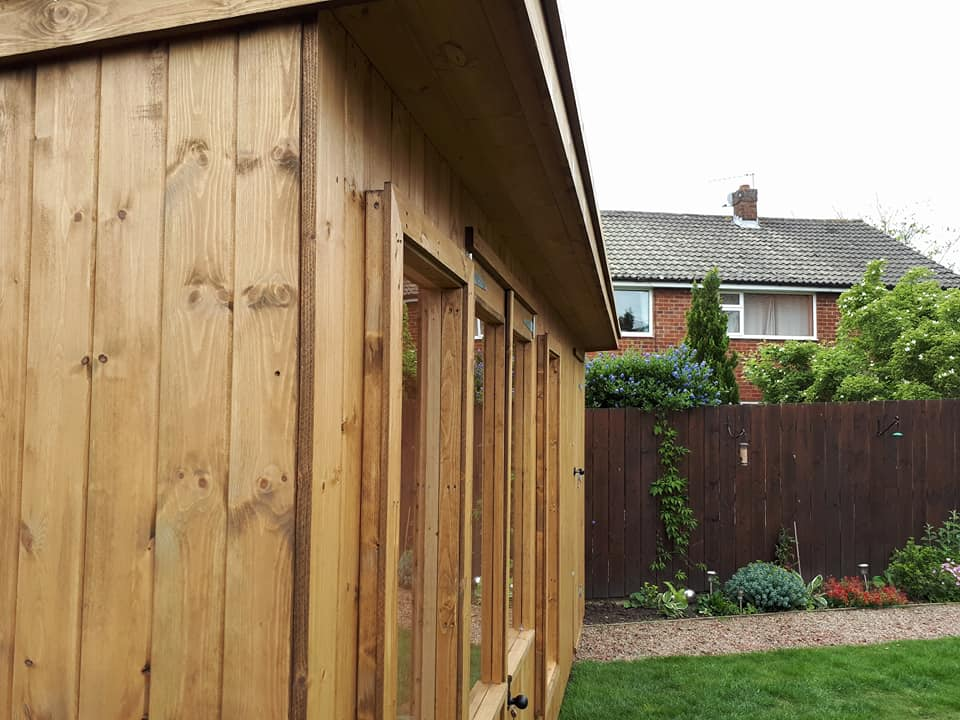 Vertical tongue and groove cladding with standard wood stain finish.